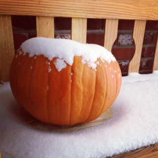 A snowy pumpkin on the porch